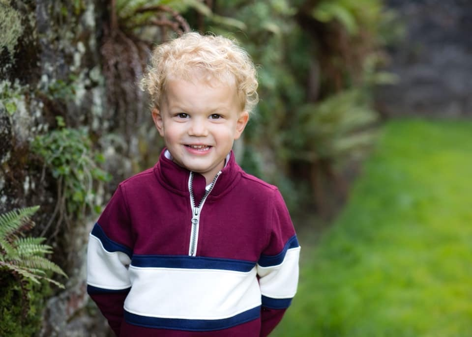 child smiling on grass needing on site childcare
